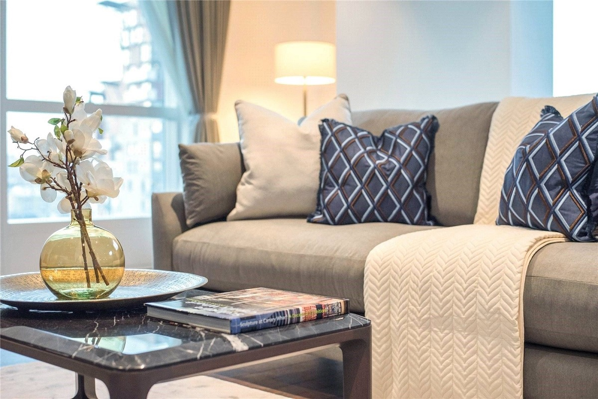 Gorgeous sitting room in London with flowers and beige sofa in stylish apartment