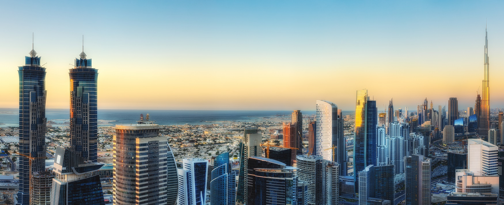 Warm and glowing view of Dubai with the sunset, skyscrapers skyline and sea.