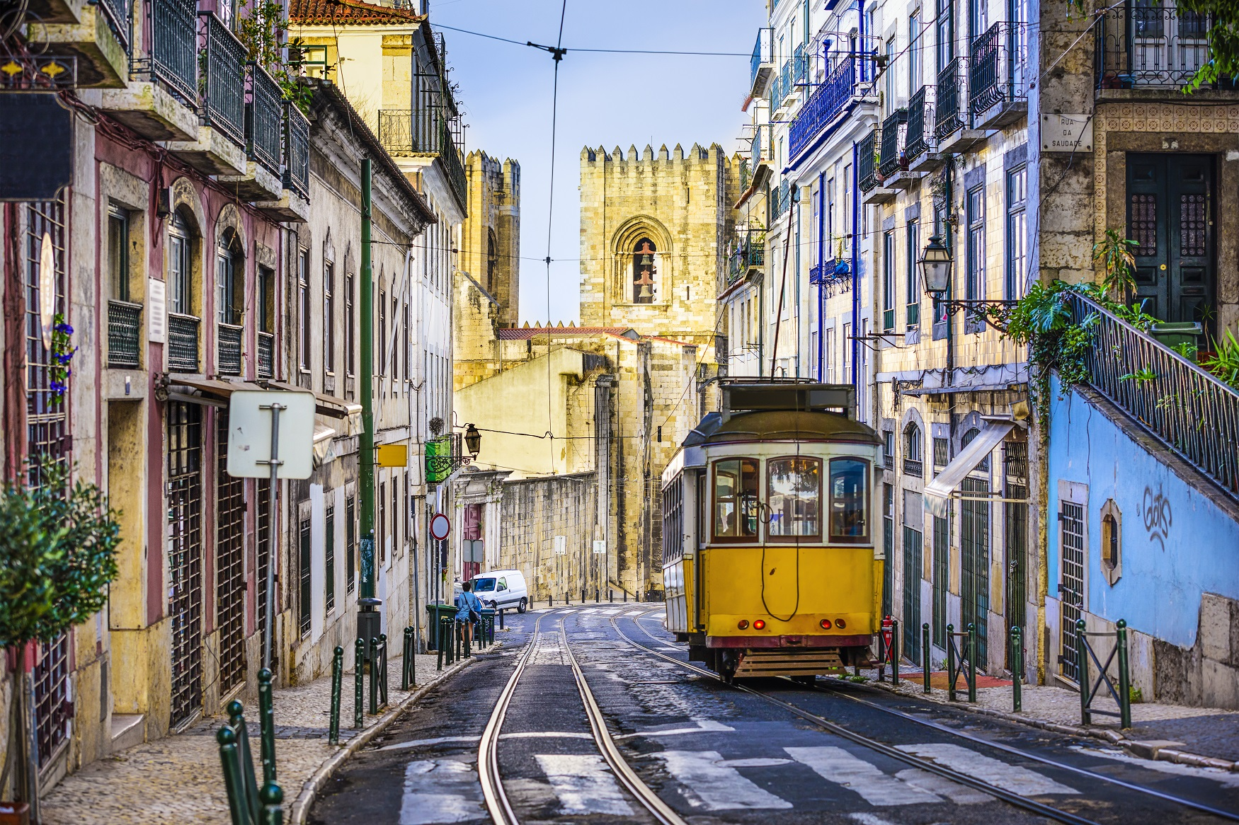 Photo of a yellow tram going down an old street in Lisbon