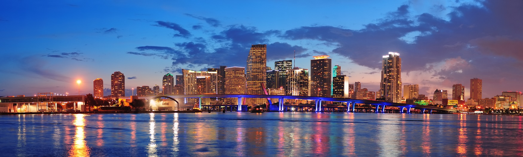 Sunset photo of the skyline in Miami with skyscrapers, bridge, sea and lots of lights.